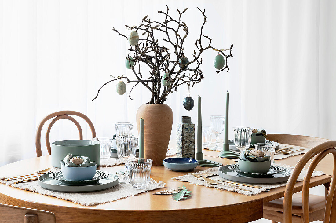 Table set simply in natural shades and decorated with branches and Easter eggs