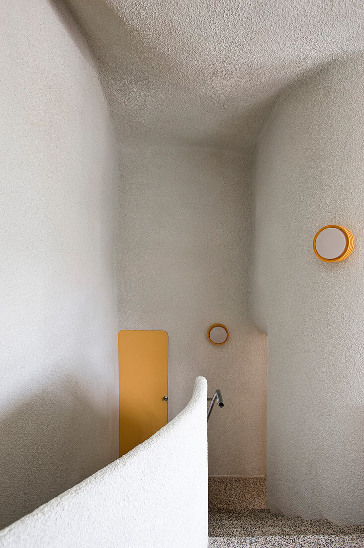 Stairwell with organically formed walls and yellow accents