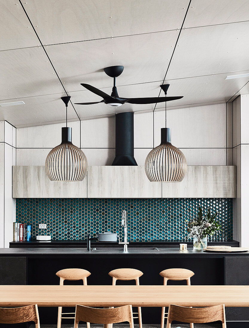View over the dining area onto the kitchen island and honeycomb-shaped tiles as splash protection