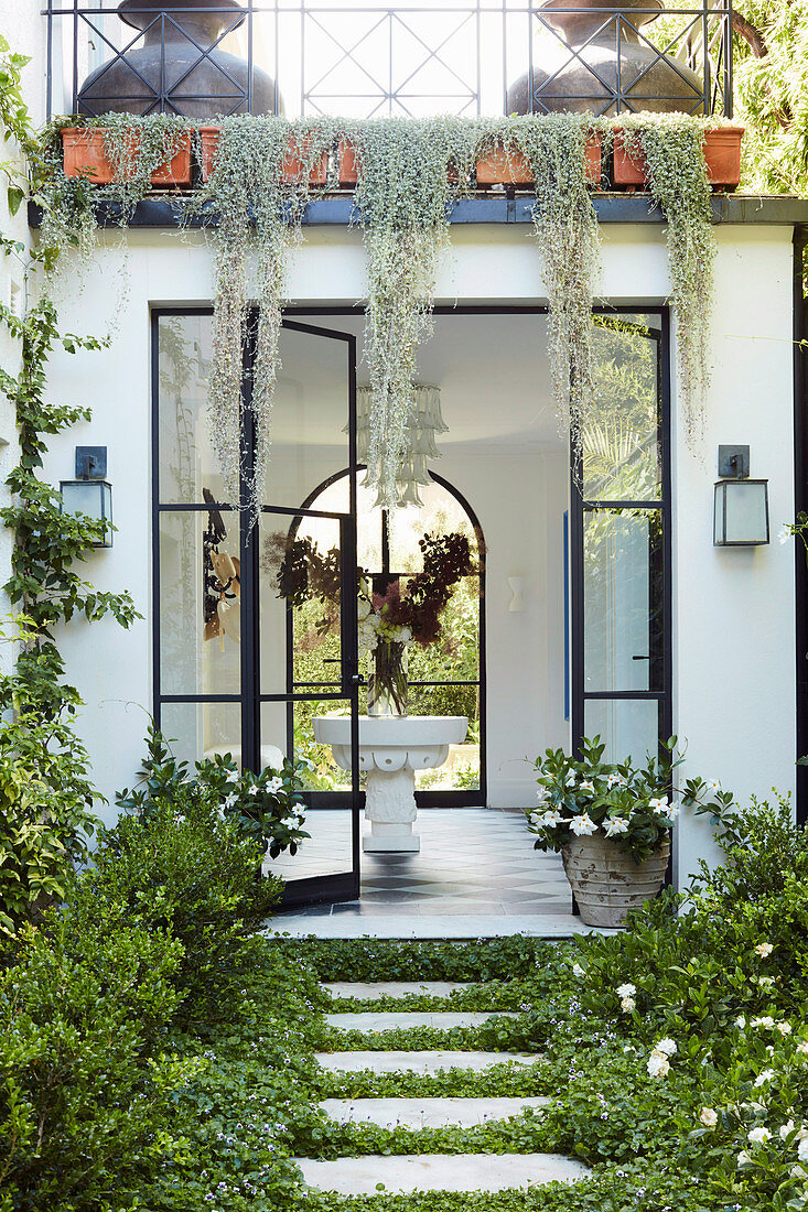 Green path leads to the entrance with a glass door