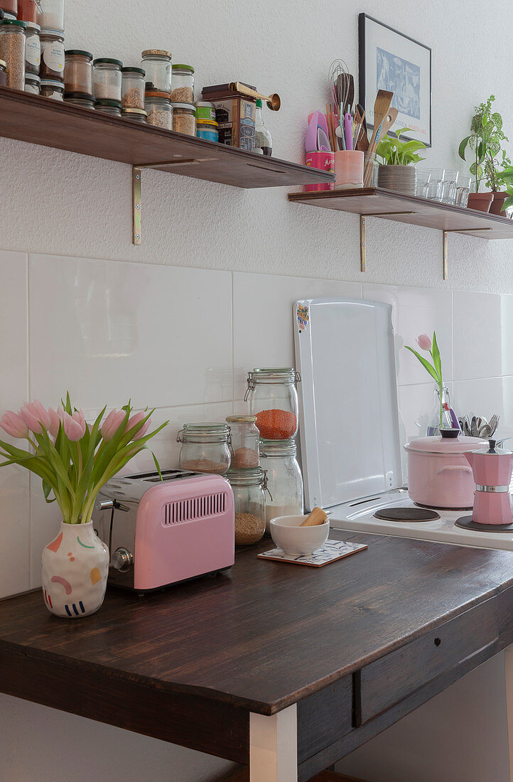 Kitchen table next to cooker below shelves in kitchen