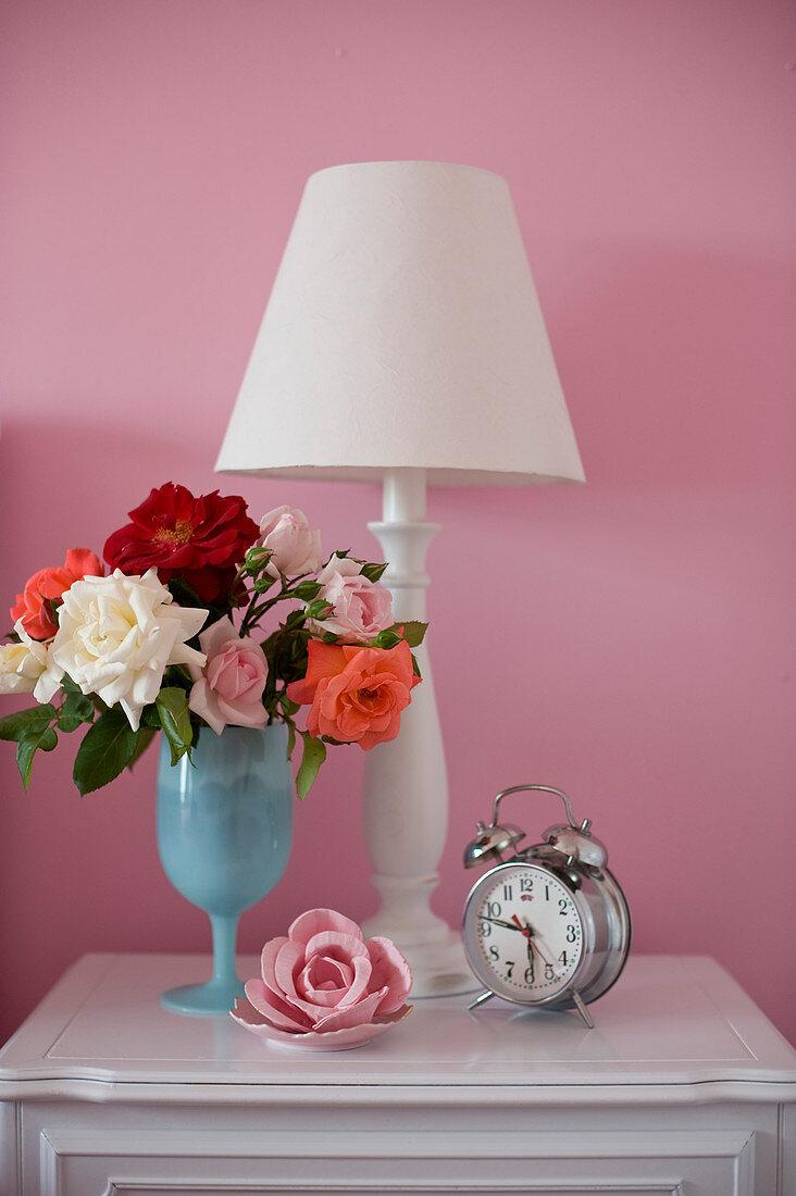 Rosenstrauß, Tischleuchte und nostalgischer Wecker auf Nachtschrank vor rosa Wand