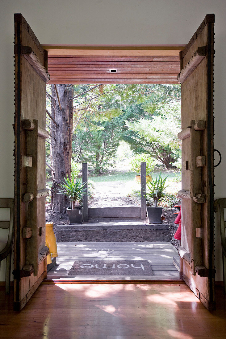 View though open, rustic, wooden double doors into summery garden