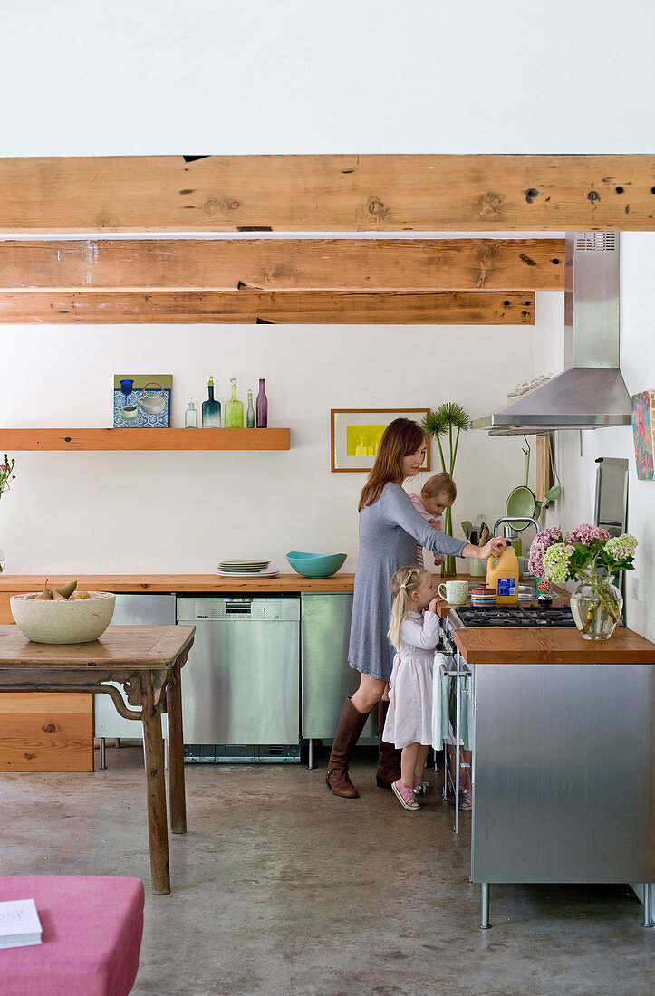 Kitchen with stainless steel cabinets and wooden worksurfaces in interior with wood-beamed ceiling