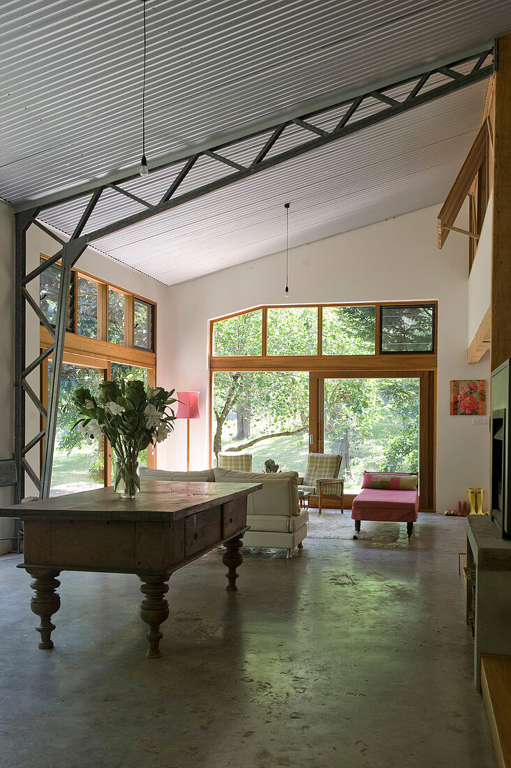Double-height interior with sloping ceiling and attractive, exposed steel joist structure