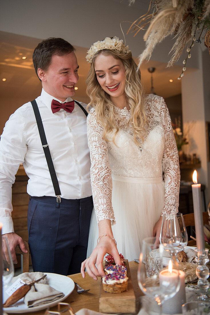 Bride and groom standing at wedding breakfast table