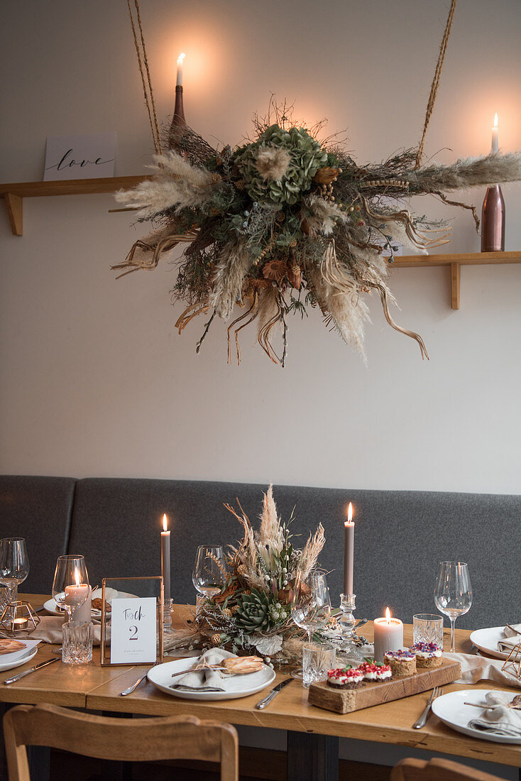 Arrangement of dried flowers suspended over table set for wedding in Industrial-style interior