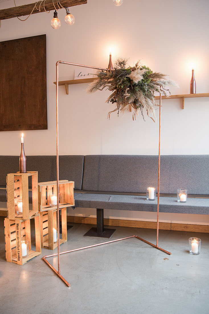 Copper wedding arch and candle lanterns in wooden crates in Industrial-style interior