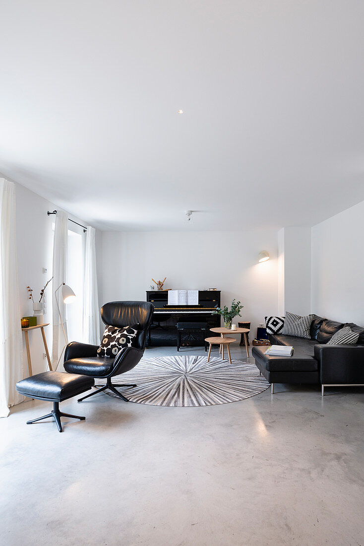 Leather armchair, piano and sofa in living room with screed floor