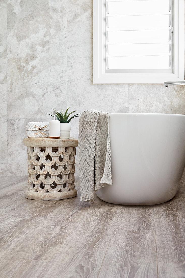 Ethnic stool next to free-standing bathtub in minimalist bathroom