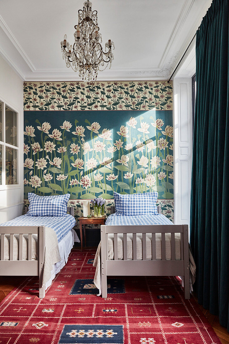 Twin beds against wall painted with water lilies