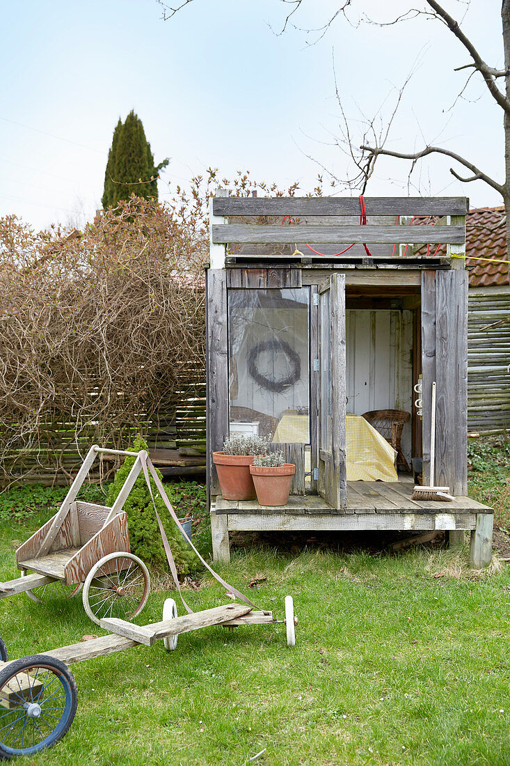 Weathered shed with roof terrace and veranda in garden