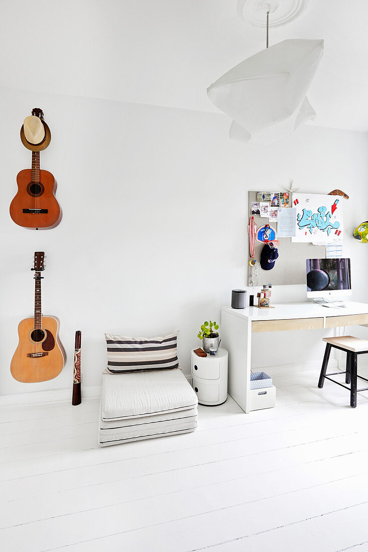 Guitars on wall, floor cushions and desk in teenager's bedroom