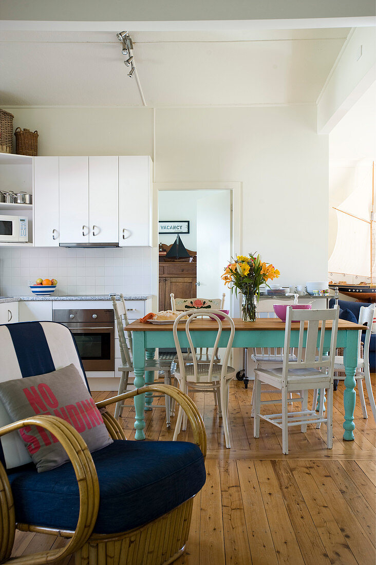 Dining table and kitchen in eclectic open-plan interior