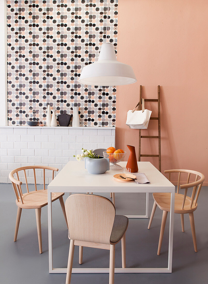 Dining area in front of ledge, patterned wallpaper and apricot wall