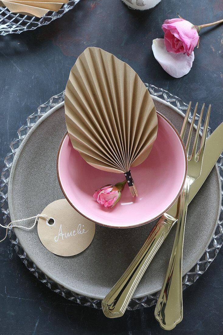 Fächer aus gefaltetem Papier in einer Schale als Tischdeko