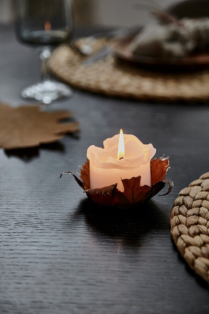 Lit candle in DIY candle holder made from autumn leaf