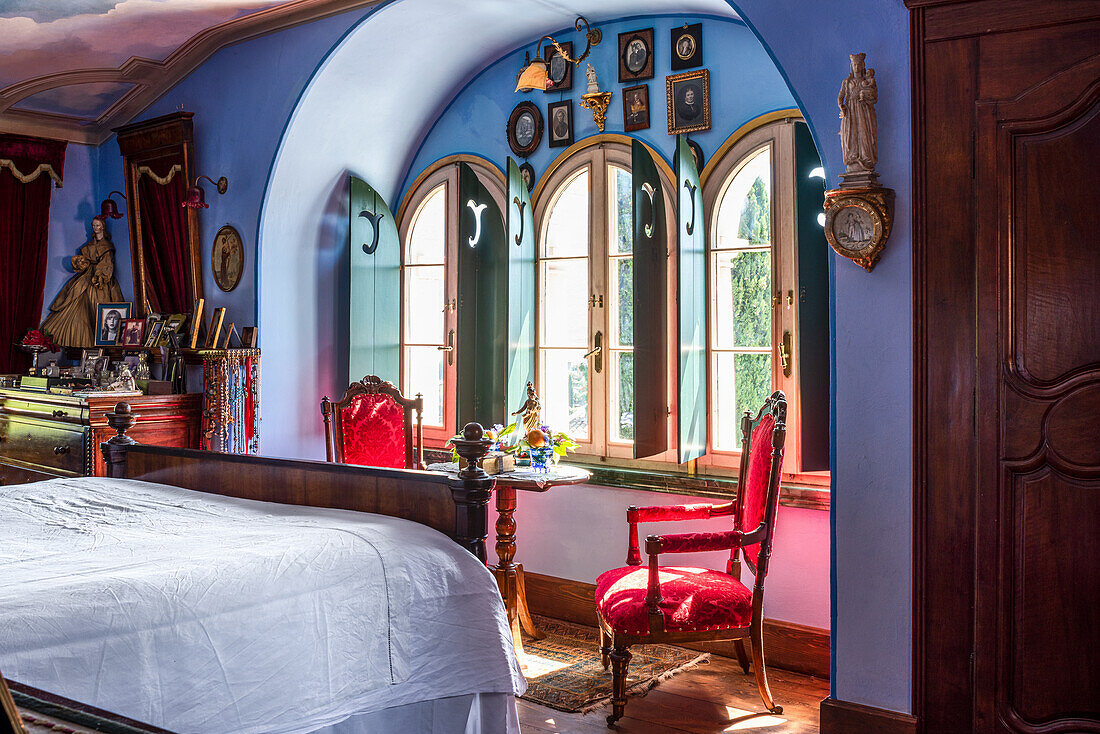 Antiques in bedroom with blue-painted walls