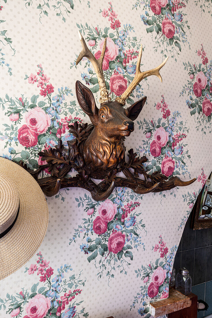 Stag's head coat rack on wall with floral wallpaper