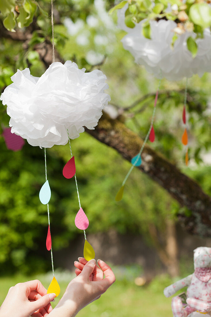 Mobile with colorful paper raindrops hanging from a cloud made of tissue paper