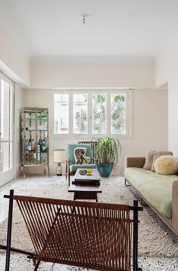 Helles Wohnzimmer mit Sofa, Designerstuhl und Vitrinenschrank