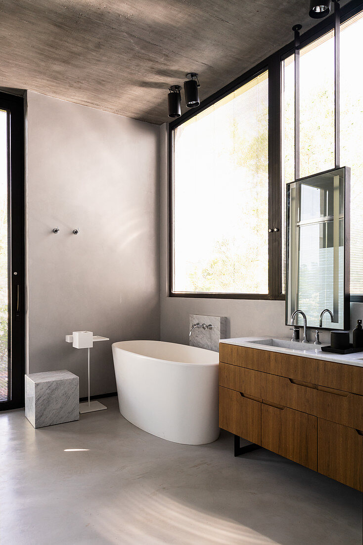 Modern, minimalist bathroom with large windows and high ceiling