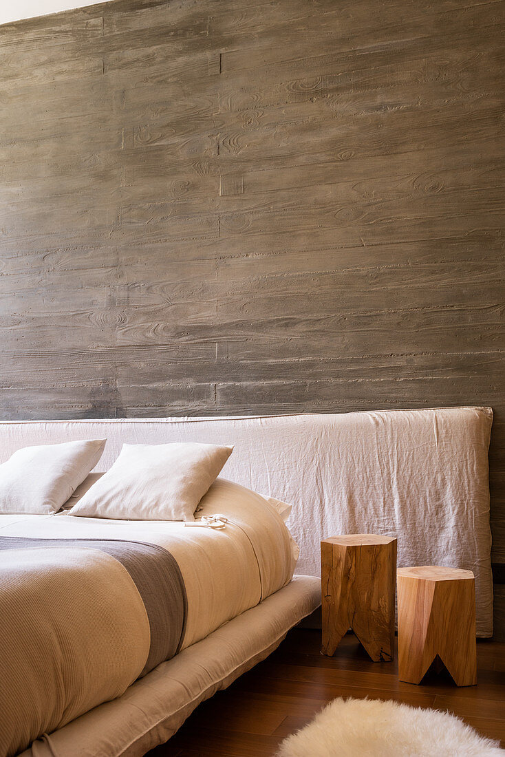 Wooden stool next to bed against board-formed concrete wall