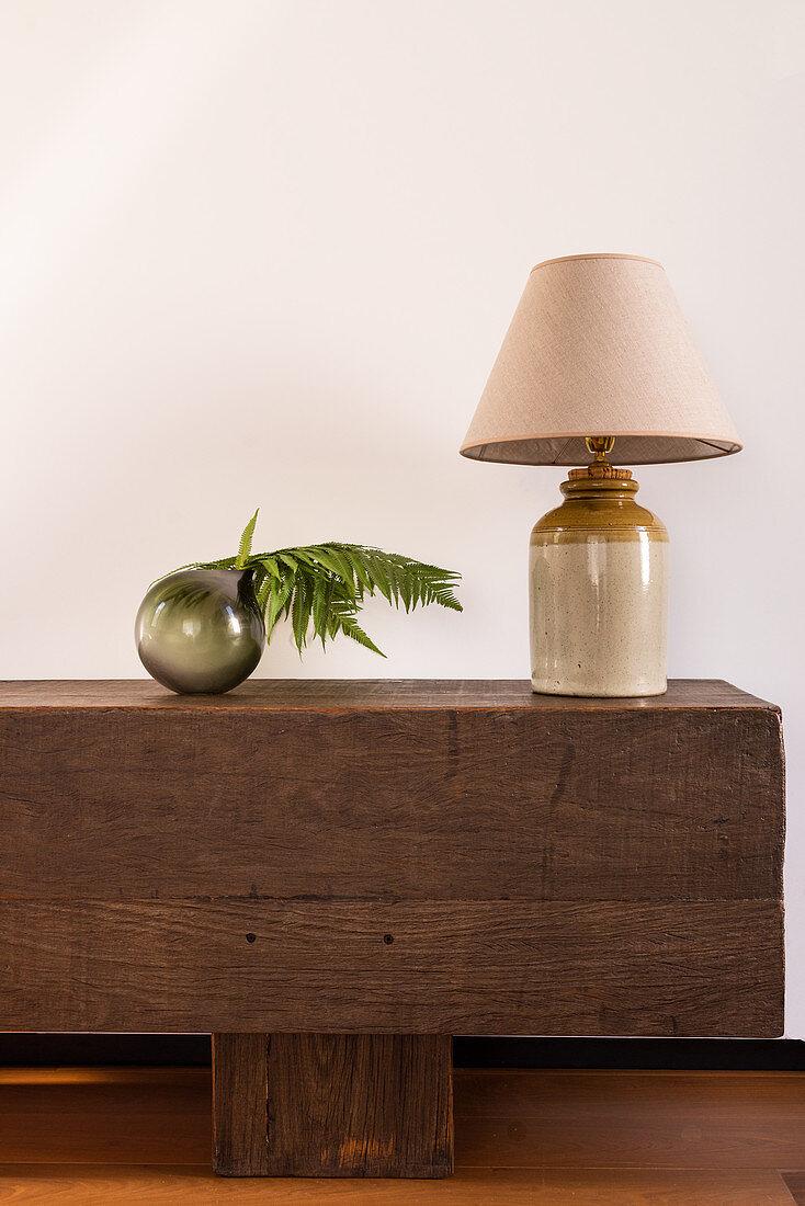 Tischleuchte und Kugelvase mit Farn auf einer Bank aus Holzbalken