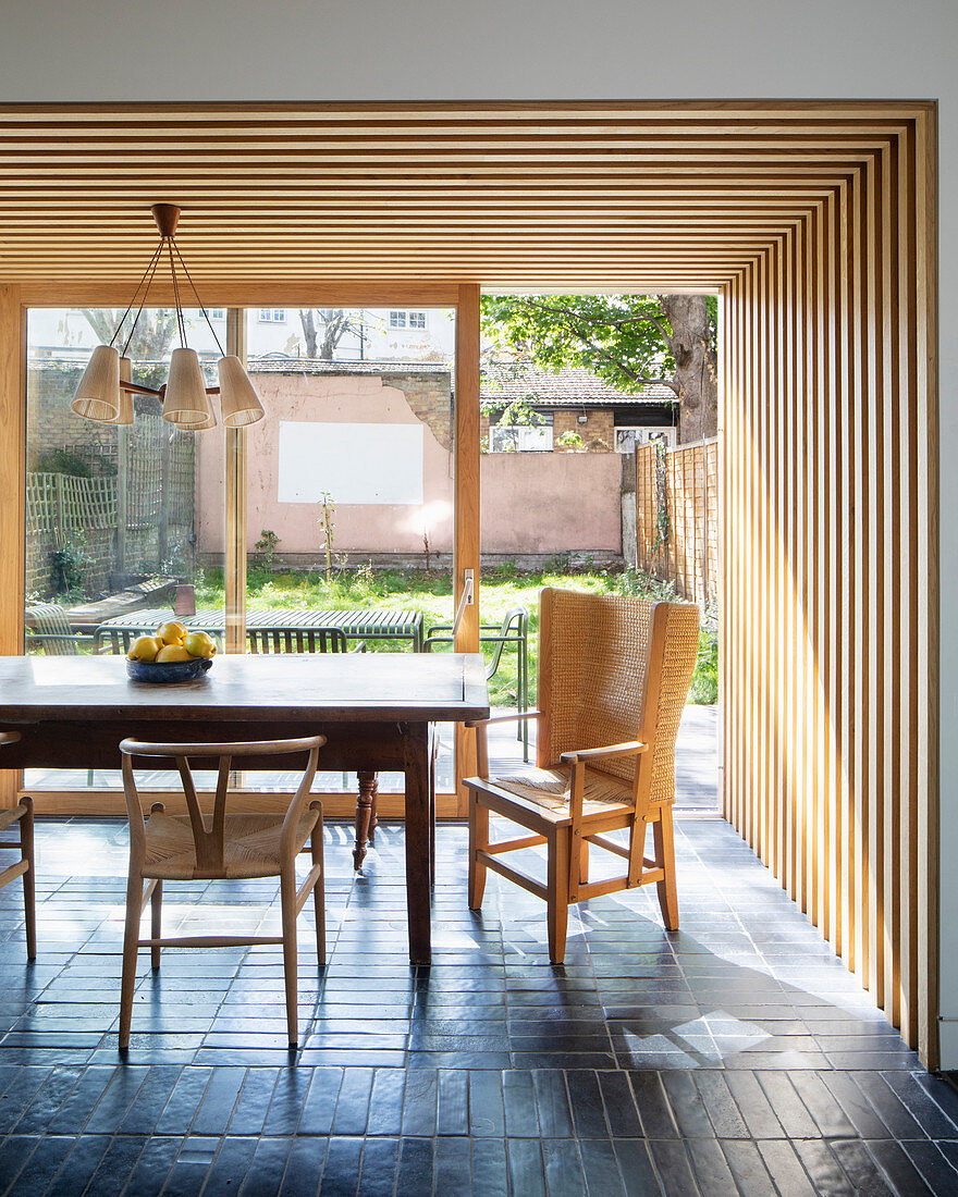 Wood-clad walls and ceiling in dining area of open-plan interior