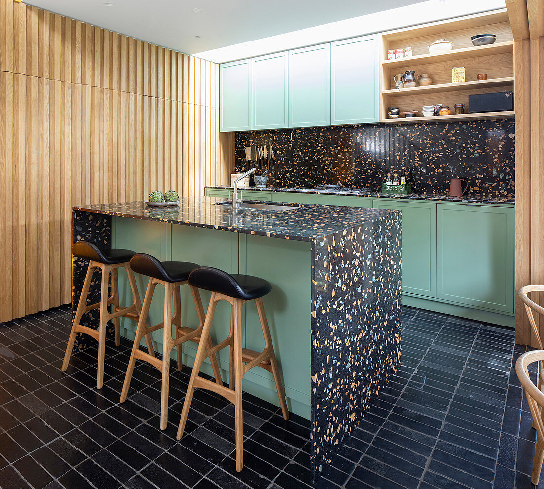 Black terrazzo island counter and green cabinets in open-plan kitchen