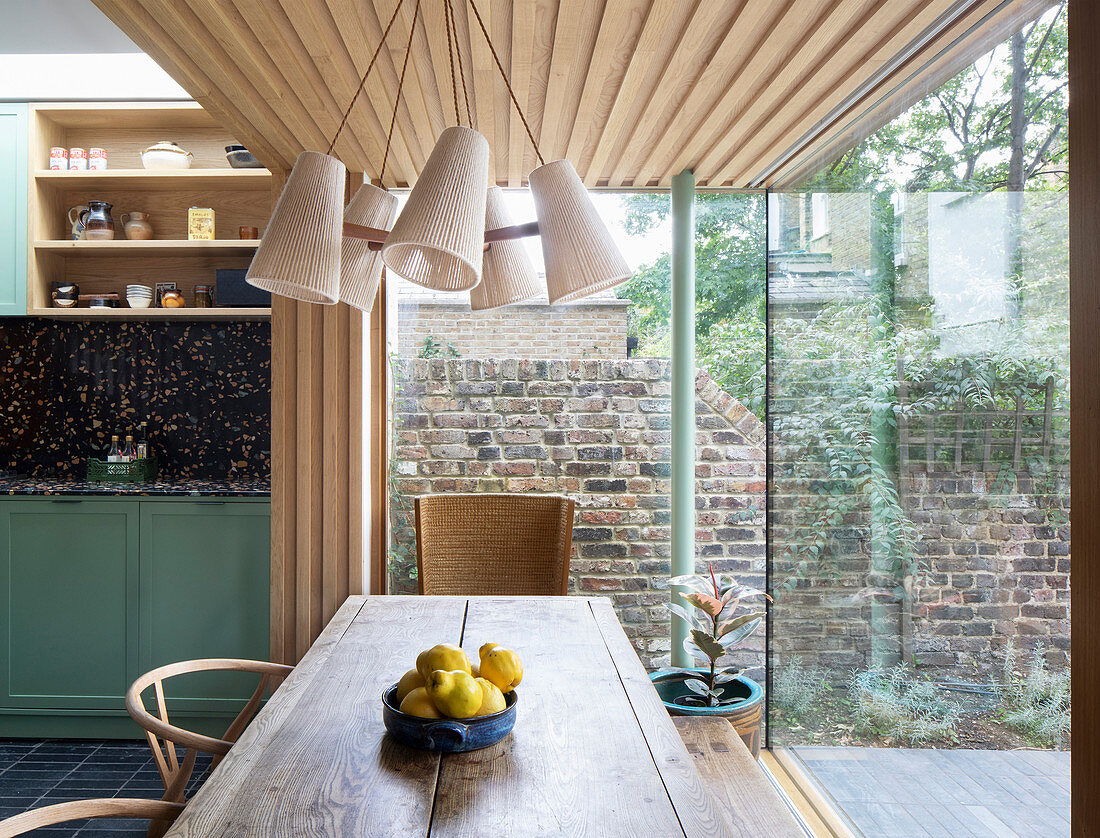 Dining area in extension with glass walls and wood cladding