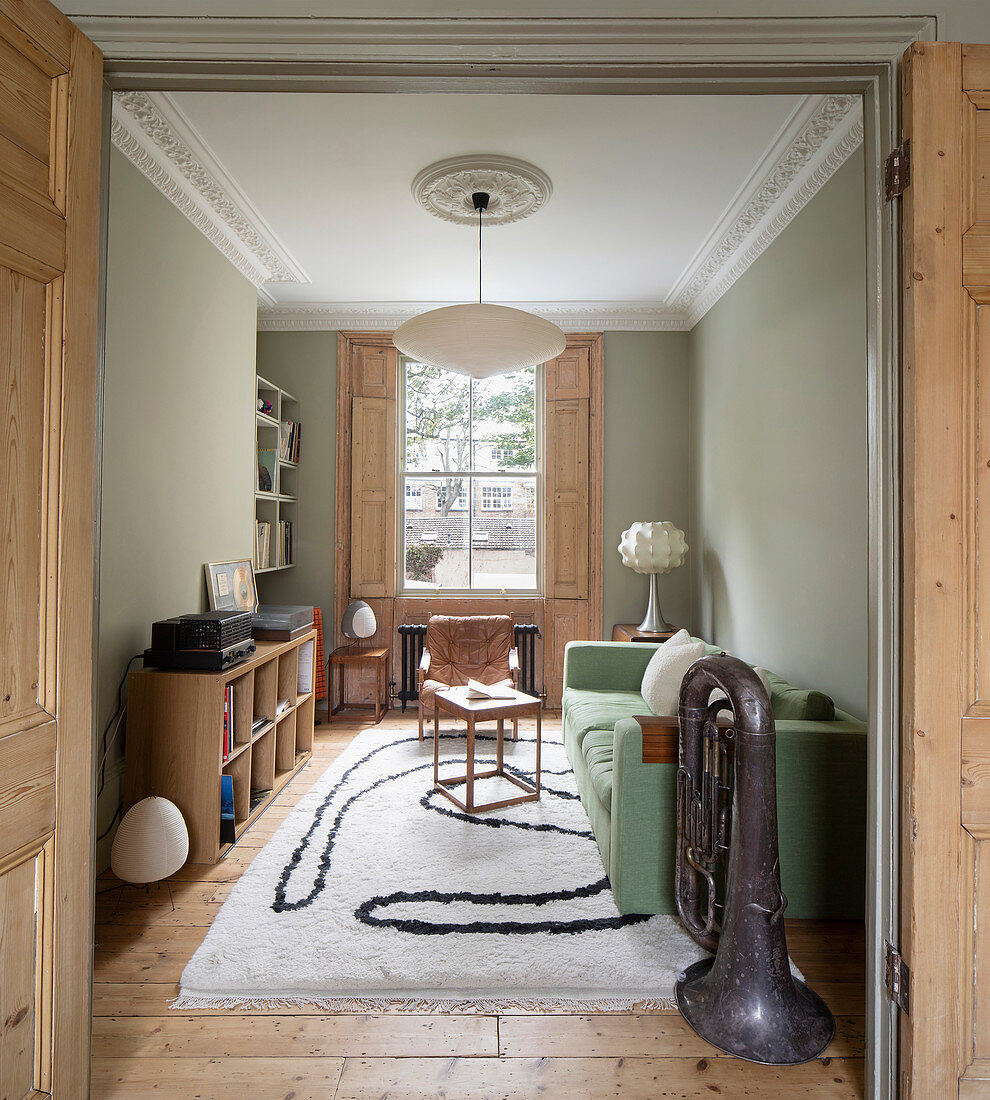 Living room in period building with stucco elements and pale green walls