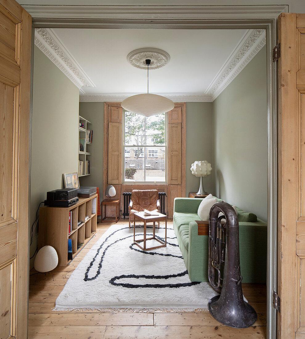 Wohnzimmer im Altbau mit Stuck und blassgrünen Wänden