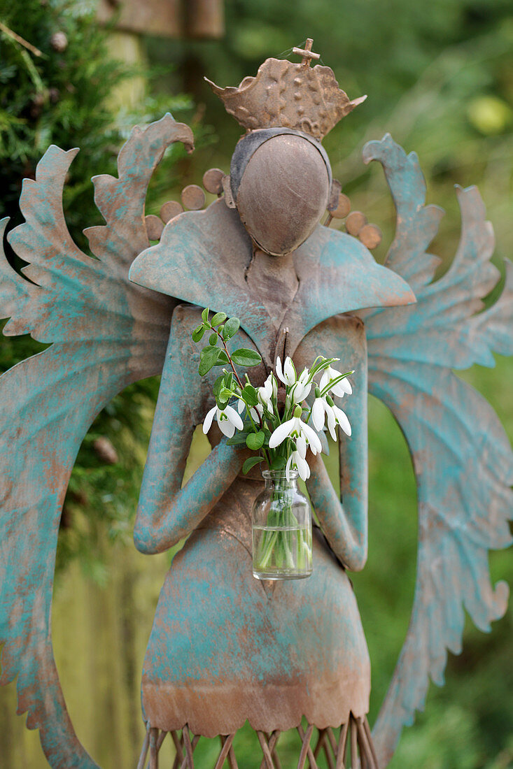 Angel holding posy of snowdrops in glass bottle
