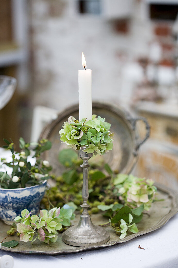 Silver candlestick with green hydrangeas as nostalgic decorations