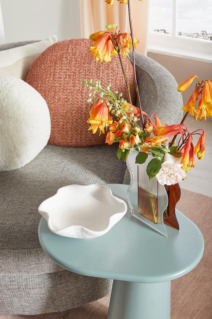 Flowers in wavy vase on light blue side table