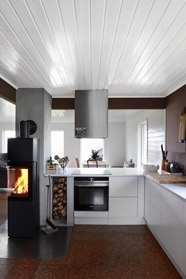 Fireplace with fire in open kitchen