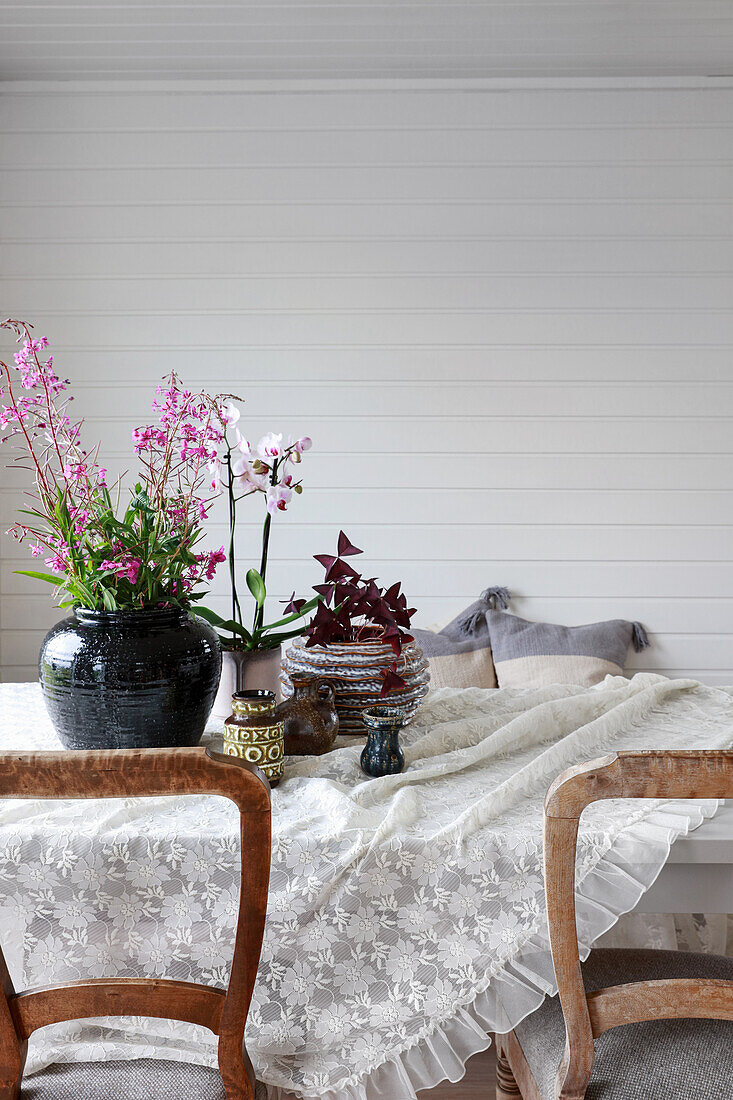 Dining table with rustic chairs in room with white lacquered wood panelling
