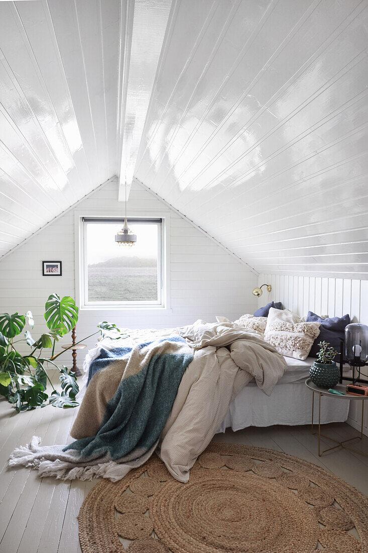 Doppelbett und Grünpflanze im Schlafzimmer mit weiß lackierter Holzverkleidung