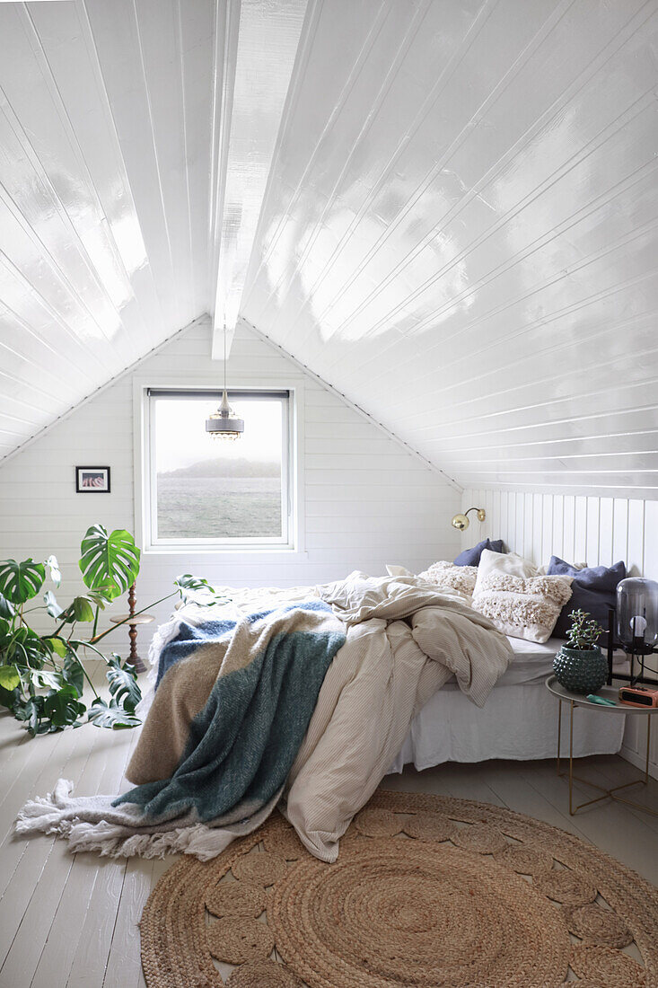 Double bed and house plant in bedroom with white-painted wood panelling