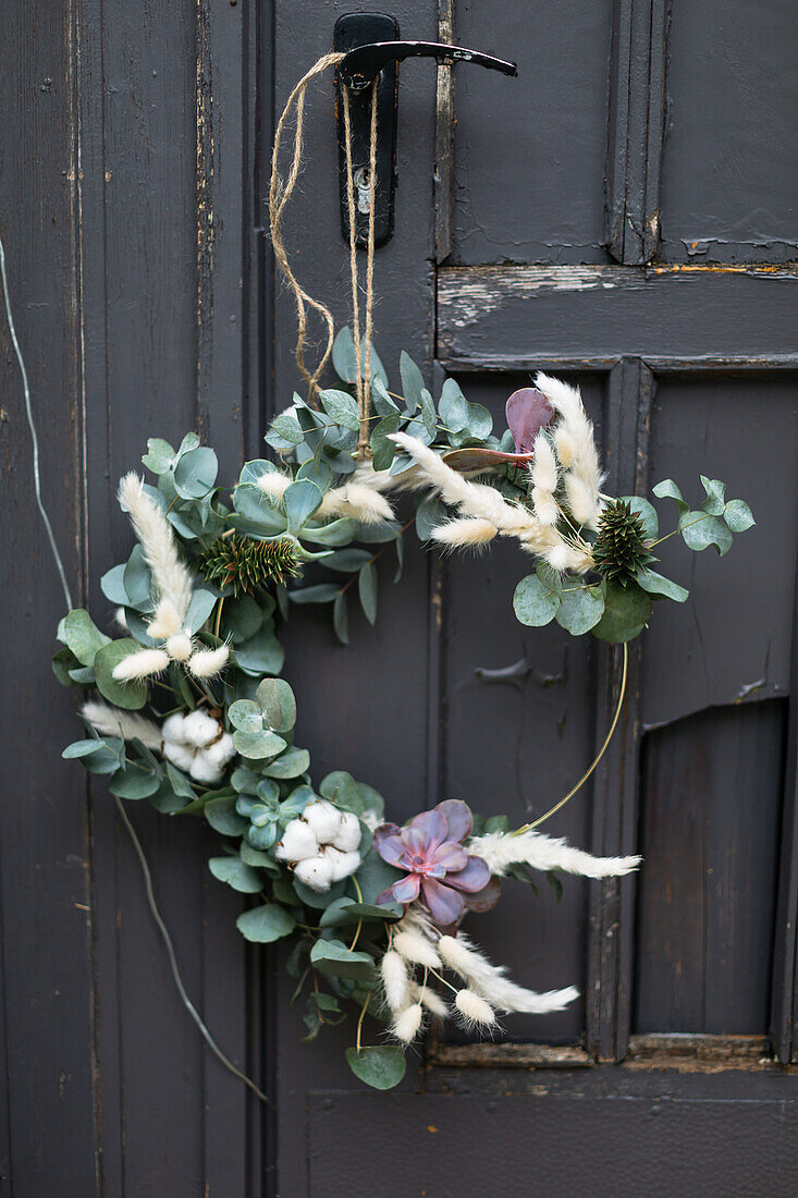 DIY wreath made of eucalyptus branches, pampas grass and Japan fir