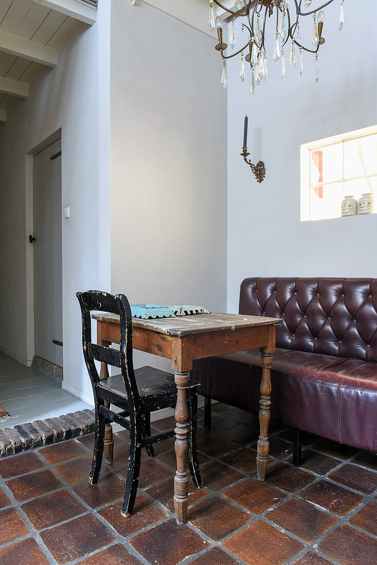 Battered chair, wooden table and leather-upholstered bench in seating area
