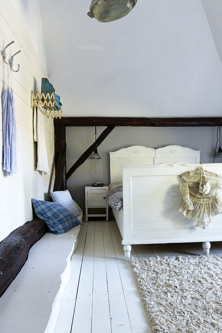 Old bed in rustic bedroom with high ceiling