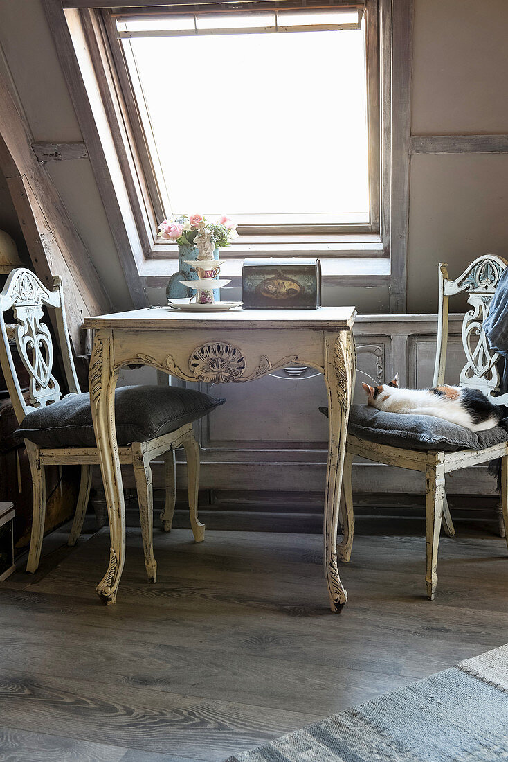 Table and chairs in shabby-chic seating area below skylight