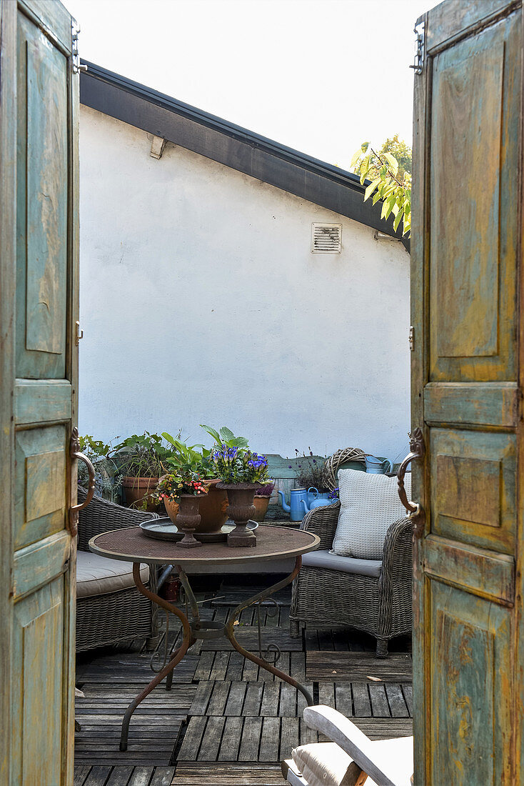 View through weathered double doors onto vintage-style roof terrace
