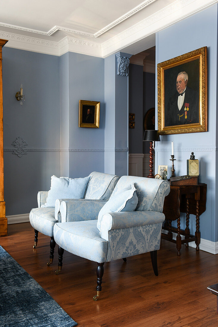 Two pale blue armchairs in classic living room with blue walls