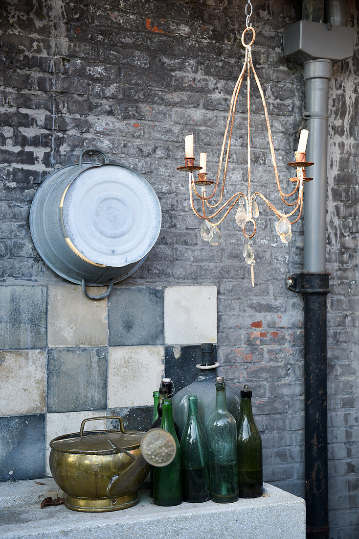 Old glass bottles and watering can on carved stone sink against brick wall