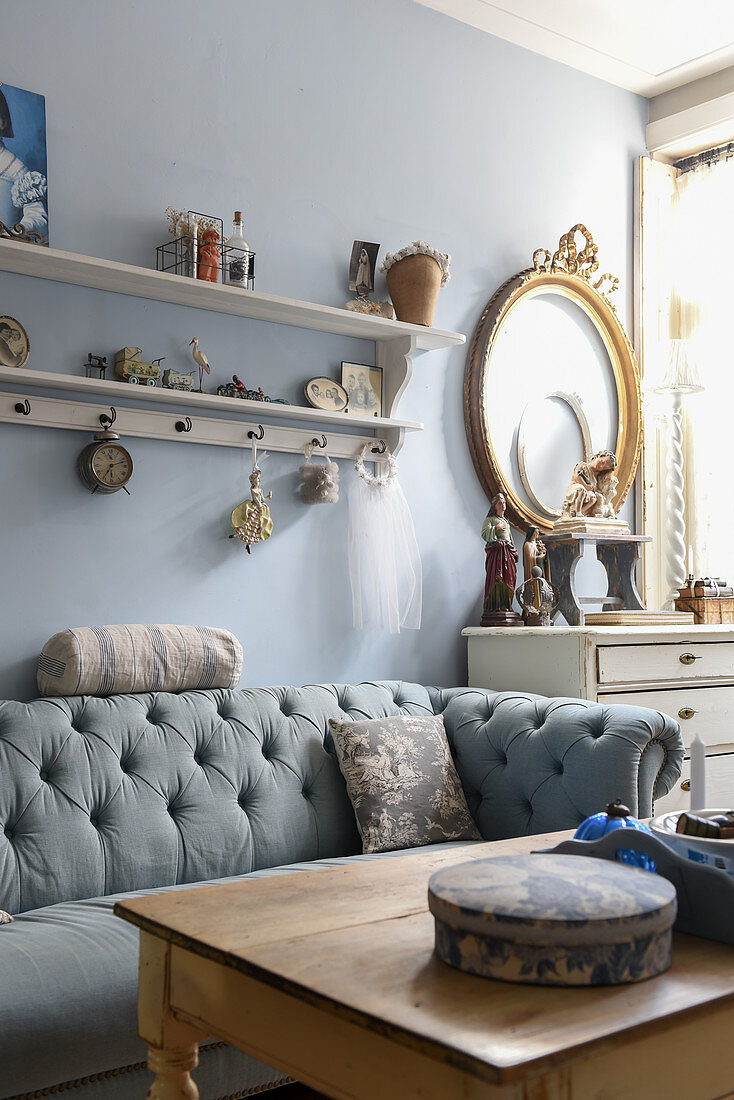 Chesterfield sofa against pale blue wall in vintage-style living room