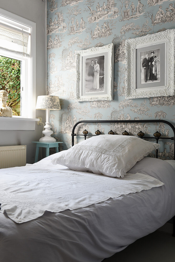 Metal bed with lace scatter cushion in bedroom with toile de jouy wallpaper