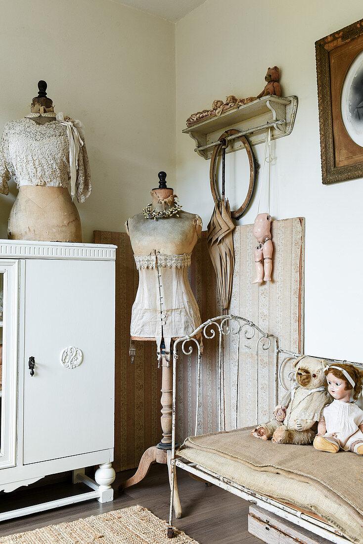 Schneiderpuppen und altes Metallbett im Wohnzimmer im Shabby Chic